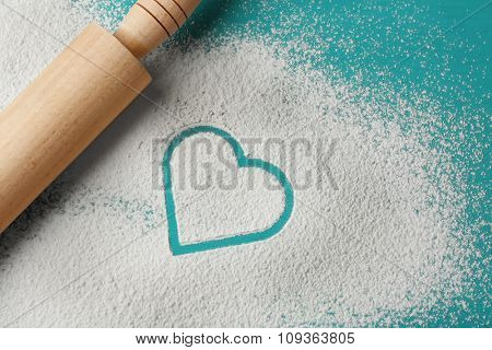 Heart of flour and rolling pin on color wooden background