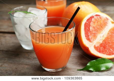 Citrus juice with ice and fresh fruits on wooden background
