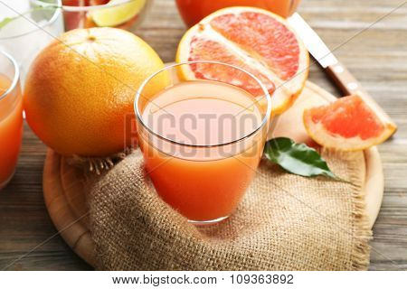 Citrus juice with ice and fresh fruits on cutting board