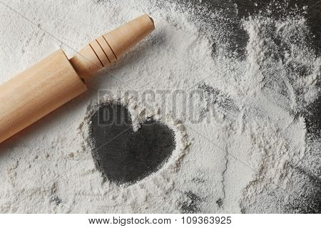 Heart of flour and rolling pin on gray background