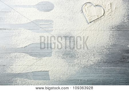 Heart of flour on wooden background