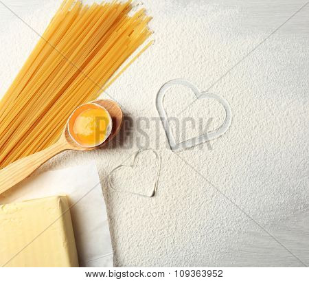 Heart of flour and pasta on gray background