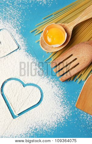 Heart of flour and pasta on color wooden background
