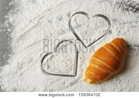 Heart of flour and fresh croissants on wooden background