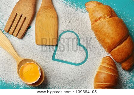 Heart of flour, croissant and  wooden kitchen utensils on color wooden background