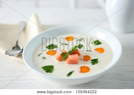 Delicious cream soup with salmon and carrot in white bowl