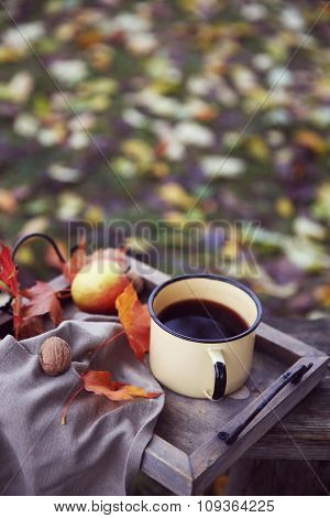 Old wooden bench with mug of coffee, fruits and nuts on mountains background