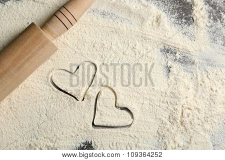 Hearts of flour and rolling pin on gray background