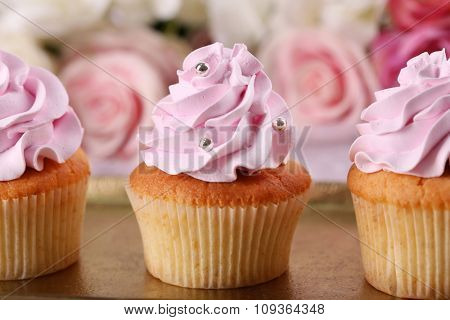 Tasty cupcakes on bright background
