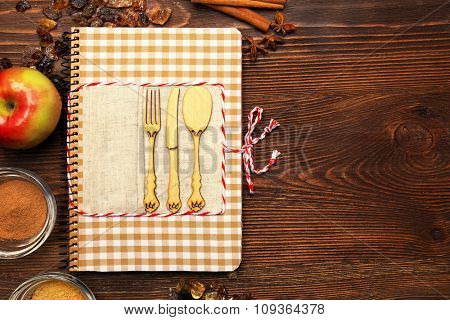 Decorated recipe book with ingredients on wooden background, copy space