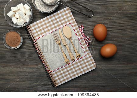 Decorated cookbook with ingredients for tasty cake on wooden background