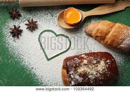 Heart of flour, croissant and  wooden kitchen utensils on green background