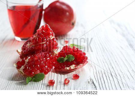 Sliced garnet fruit and tasty juice, on wooden background