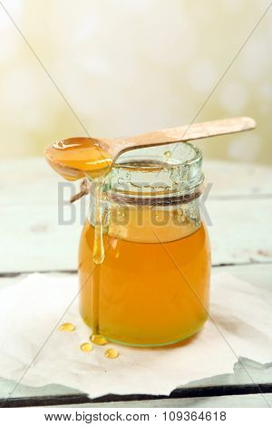 Honey jar with wooden spoon on light background