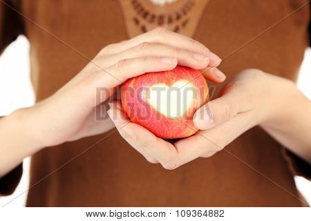 Red apple with heart in female hands close-up