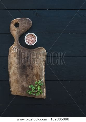 Kitchen-ware set. Old rustic chopping board made of walnut wood, salt and oregano herb on a black ba