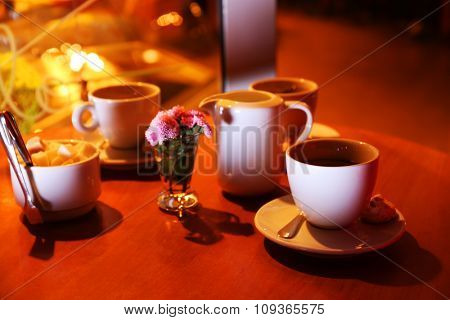 Served wooden table with cups of coffee and sugar on the street at night