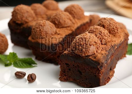 Pieces of chocolate cake with mint on the table, close-up