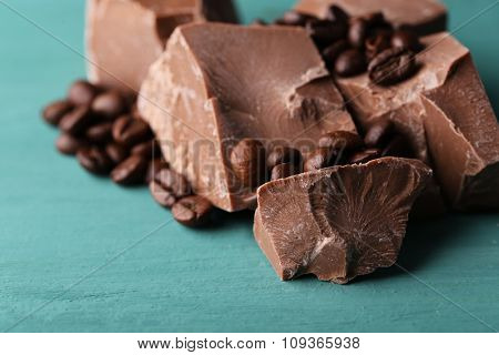 Milk chocolate pieces and coffee grains on color wooden background
