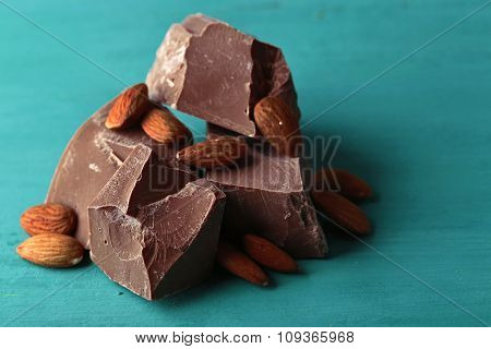 Milk chocolate pieces with almonds on color wooden background