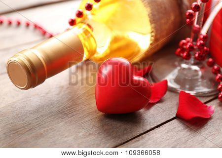 A bottle of white wine and decorations, on wooden background, close-up