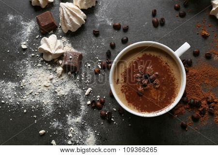 Cup of coffee and sweets on black wooden background