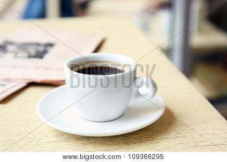 Cup of tasty coffee and newspaper on cafe background