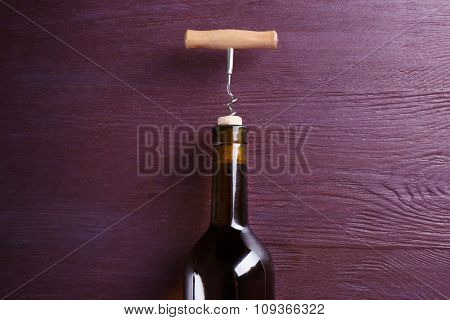 Corkscrew and wine bottle on purple wooden background