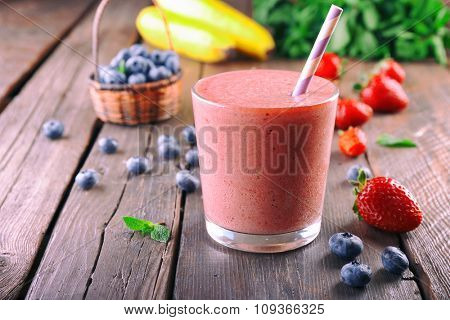 A glass of fresh cold smoothie with berries, on wooden background