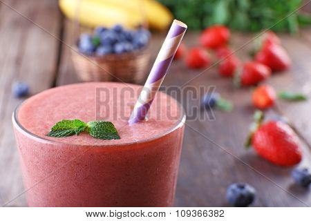A glass of fresh cold smoothie with berries and mint, on wooden background, close-up