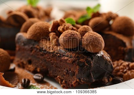 A piece of chocolate cake with walnut and mint on the table, close-up