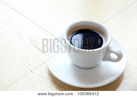 Cup of tasty coffee on table