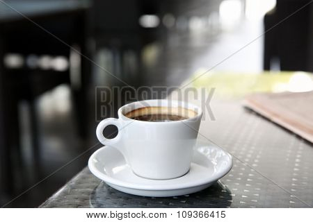 Cup of tasty coffee and newspapers in cafe