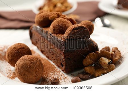 Chocolate balls and a piece of cake with walnut on the table, close-up