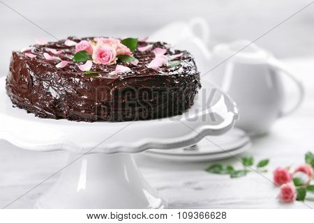 Chocolate cake decorated with flowers on the table