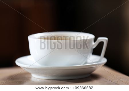 Cup of coffee in the table on defocused background