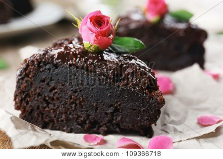 Piece of chocolate cake decorated with flowers on brown wooden table, close-up