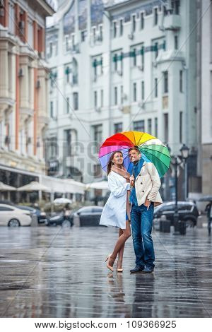 Smilig couple with an umbrella on the street