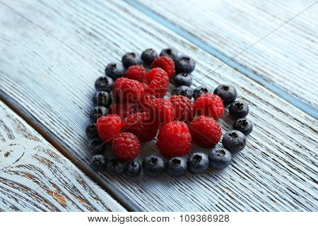 Heart shaped raspberries and blueberries on old wooden background