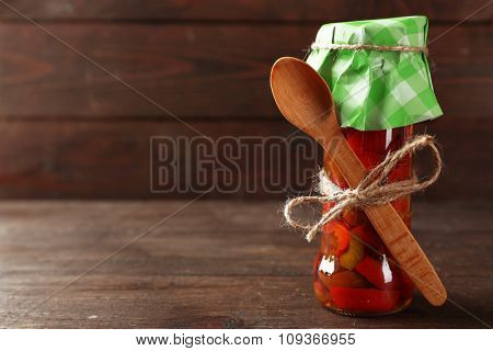 Canned red peppers in glass jar on wooden background