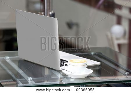 View on laptop and a cup of coffee on glass table, close-up
