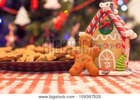Cute gingerbread man and candy ginger house background Christmas tree lights
