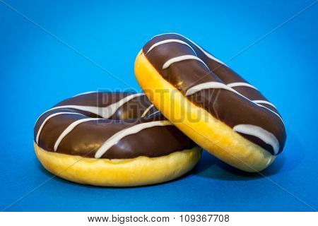 Two chocolate donuts on the blue background