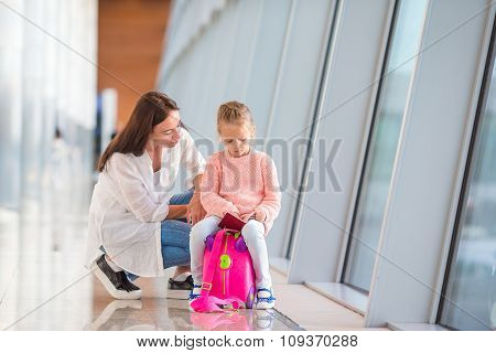 Mother and little girl with boarding pass at airport waiting the flight