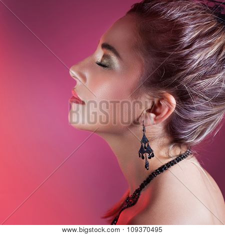 Side view portrait of gorgeous female with closed eyes over pink background, wearing elegant earrings and necklace, fashion look for Christmas party