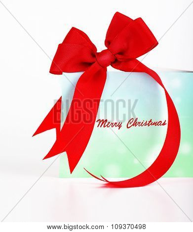Merry Christmas greeting card, beautiful blue and green postcard with red ribbon bow over white background, wishing happy holidays