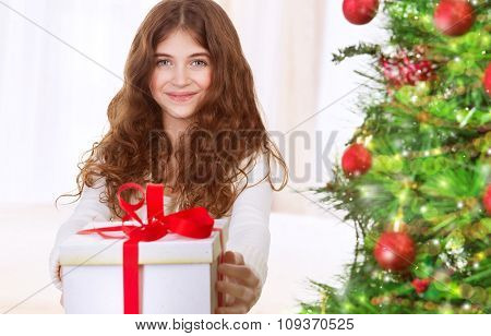 Portrait of cute happy teen girl with gift box standing near beautiful decorated Christmas tree, with pleasure celebrating winter holidays