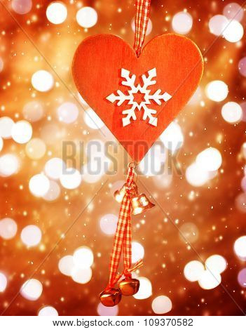 Beautiful red heart shaped Christmas decoration with snowflake ornament hanging on blur shiny background, stylish christmastime bauble