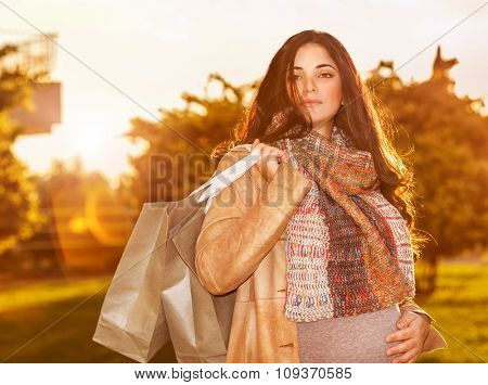 Portrait of cute pregnant woman with shopping bags standing on backyard in warm autumn sunny day, preparing to child birth