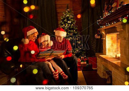 Happy family reading a book by a Christmas tree in cozy living room in winter
